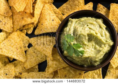 Homemade fresh guacamole sauce with corn chips top view
