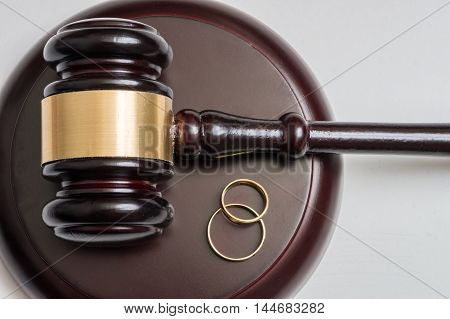 Closeup view on golden rings and gavel in background. Divorce concept.