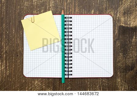 Open notebook with sticky note and pencil on wooden background