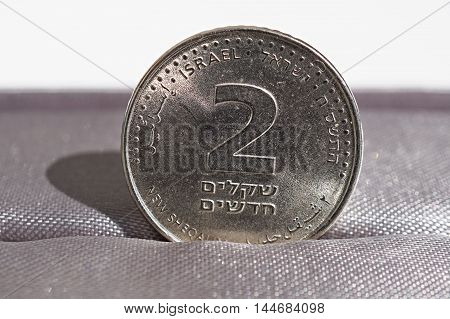 Macro detail of a metal coin of two Shekels (Israeli currency New Shekel, ILS) placed in the gift box as a symbol of luxury and highly appreciated currency of Israel