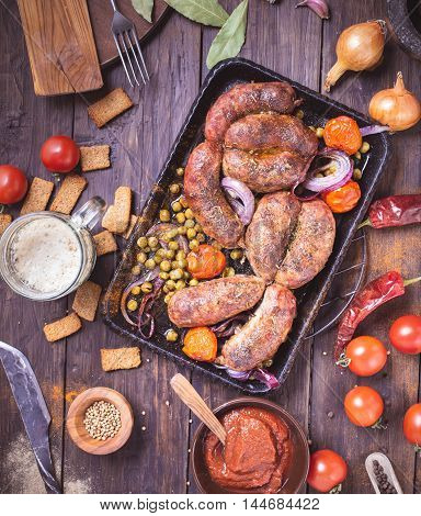 Homemade baked sausages with pea and tomatoes on table top view. Toned