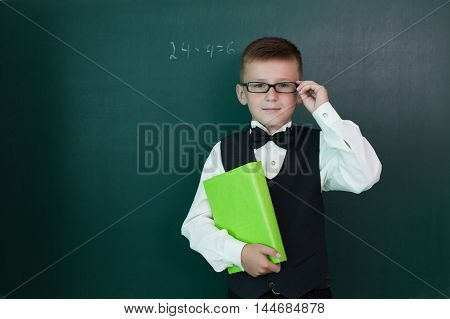 Happy pupil with schoolbook on the blackboard
