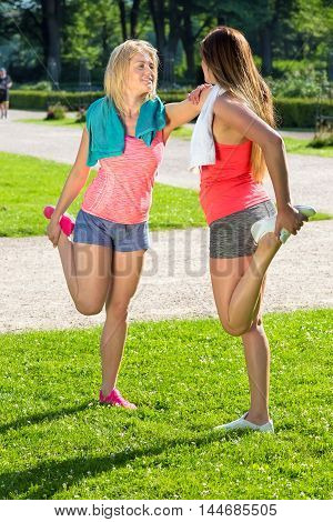 Pair Of Joggers Stretching Their Leg Muscles