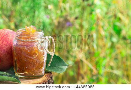 Jar of apple jam at left side outdoor