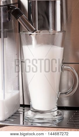 Automatic coffee with milk preparation closeup shot