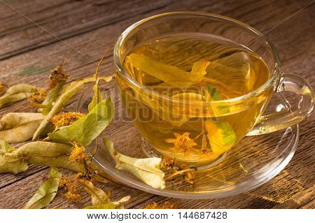Cup of linden flowers tea on old wooden table