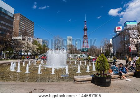 SAPPORO HOKKAIDO JAPAN - APRIL 24 2016: Unidentified people at the Fountain of Odori park in front of Sapporo TV tower.