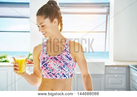 Smiling gorgeous young woman holding a glass of fresh healthy fruit juice she has just prepared from apples and citrus in a bright light clean kitchen