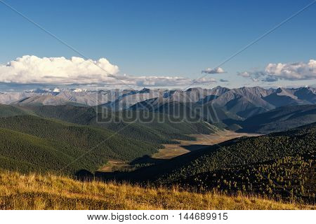 The picturesque top view on the mountain peaks slopes of the mountains covered with forests and the valley between the mountains on the background of blue sky and clouds
