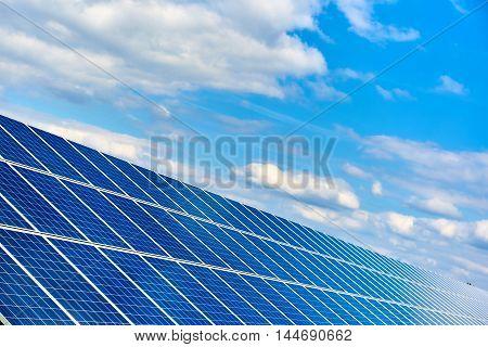 Blue solar panels against blue cloudy sky