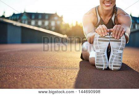 Woman athlete grabs her shoes as she stretches and smiles while seated on jogging path