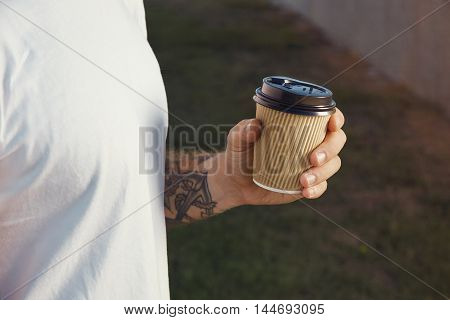 Tattooed Man Holding A Paper Coffee Cup