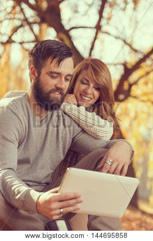 Couple in love sitting on autumn fallen leaves in a park surfing the net on a tablet computer
