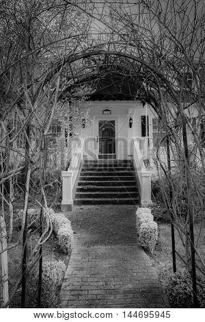Archway and sidewalk leading to an old white house surrounded by bare trees, Black and white.