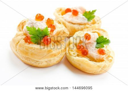 Appetizer with red caviar gourmet food party snack. Profiterole with fish mousse or pate and red caviar close up isolated on white background
