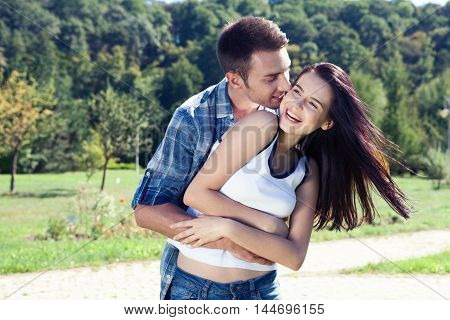 Portrait of happy young couple looking at each other and smiling outdoor closeup