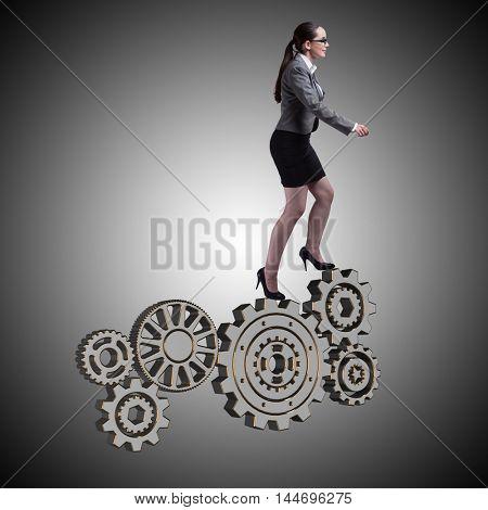 Busineswoman with cogwheels gear in teamwork concept