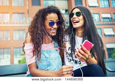 Beautiful young friends in city laughing while listening or viewing something humorous on their cell phone