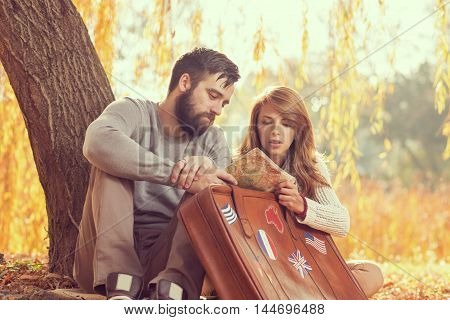 Couple in love sitting on autumn fallen leaves in a park looking at the map getting ready for sightseeing on their travel tour