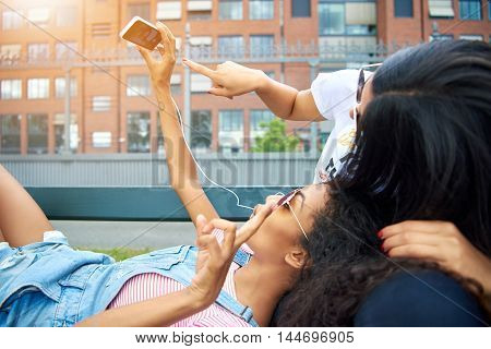 Beautiful woman in overalls takes photo on bench with their digital device