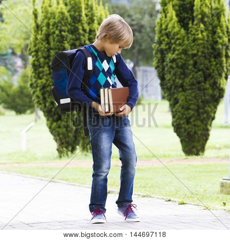 Serious focused child with backpack carring books in his hands. Outdoor. Education back to school people concept. Square format image