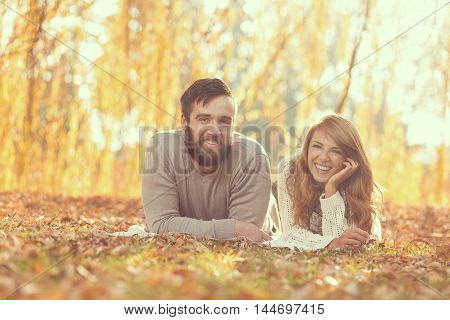 Couple in love lying on fallen autumn leaves under a tree in a park enjoying a wonderful autumn day in nature