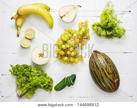 collection of green vegetables and fruits on white wooden background. Top view