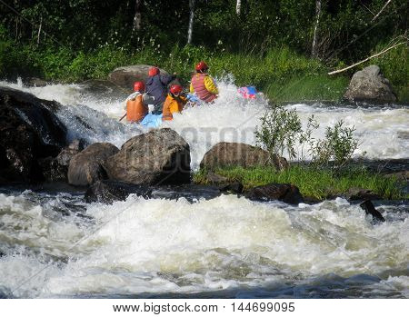 KOLA PENINSULA RUSSIA - 16 AUGUST 2008: Four men on an inflatable catamaran overcome the threshold of the turbulent river. Catamaran is not visible.