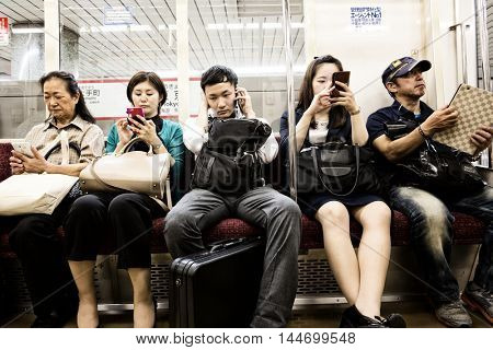 TOKYO, JAPAN - 24 JUNE 2016 - Commuters with their mobile phones on a subway train in Tokyo, Japan. High contrast processing.