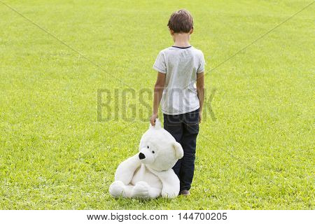 Sad young boy is holding a teddy bear and standing on the meadow. Child looking down. Back view. adness fear frustration loneliness concept
