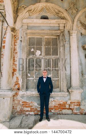 Handsome groom in blue suit stands in front of ruined window at ancient abandoned palace.