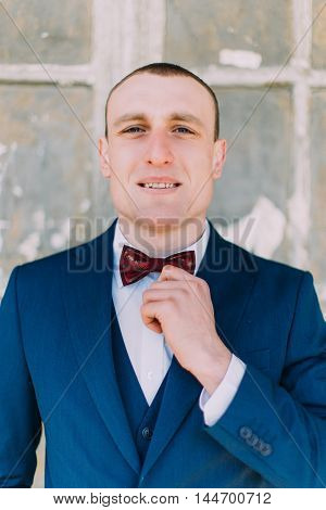 Handsome groom in blue suit stands smiling in front of ruined window at ancient abandoned palace.