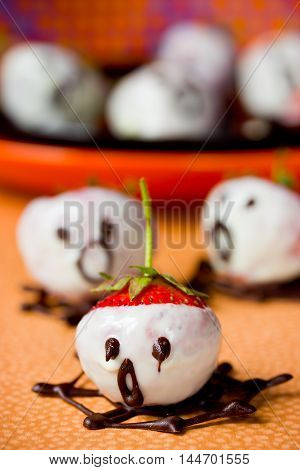 Halloween treats and sweets ghosts made from strawberries and chocolate selective focus