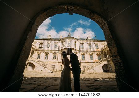 Passionate enloved couple share romantic at entrance arch of magnificent looking baroque palace shined by bright summer sun rays.