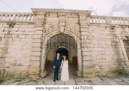 Newlywed couple pose at old ruined gate of baroque castle wall.