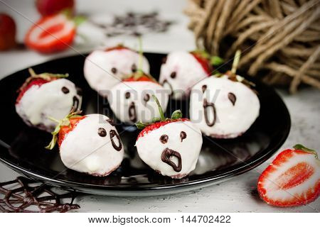 White chocolate strawberry ghosts for Halloween party selective focus