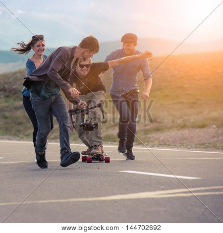 Friends run, laugh and shoot with the camera on the electronic suspension, the man on the longboard