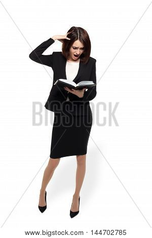 Beautiful business woman is shocked and upset by reading her diary. The concept of time management. Isolated on white with clipping path.