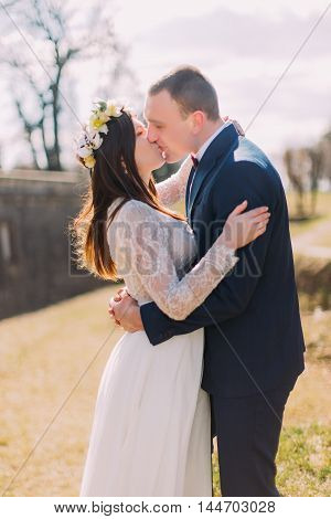 Close-up of happy stylish newlywed couple embracing and kissing outdoor.