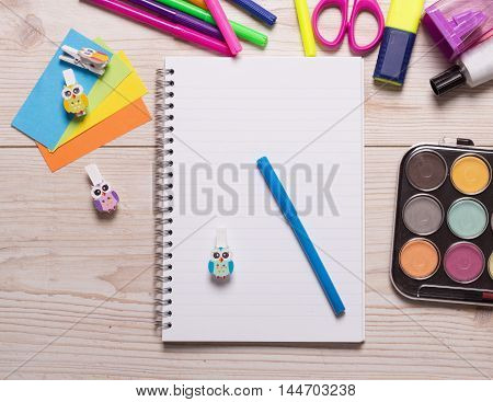 Blank notebook with marker and other school supplies on wooden desk