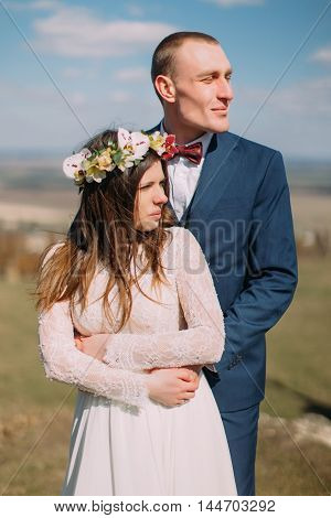 Wedding portrait of happy stylish newlywed bride and groom hugging outdoor with cloudy sky at background.