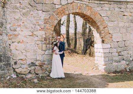 Newlywed couple pose at old ruined gate of ancient baroque castle wall.