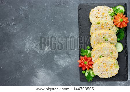 Festive meal - diet roll of rabbit or chicken mince with vegetables on a black stone plate top view blank space for text
