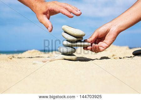 Man and woman together to build a tower made of stones. Couple together build their future