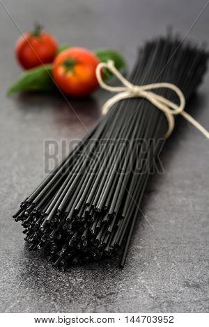 Black spaghetti, basil and tomatoes on black slate background