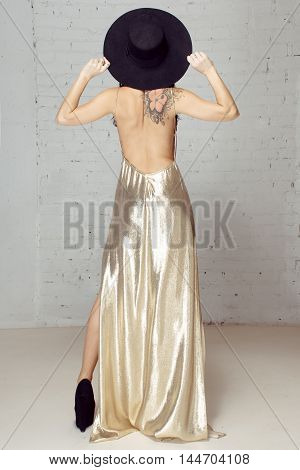 Girl in black hat staying turning away from photographer in studio near brick wall The girl in gold dress and black hat