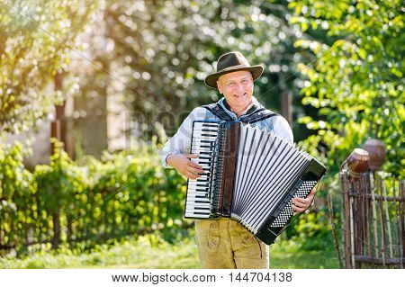 Man in traditional bavarian clothes standing in the garden in front of wooden fence playing accordion. Oktoberfest.