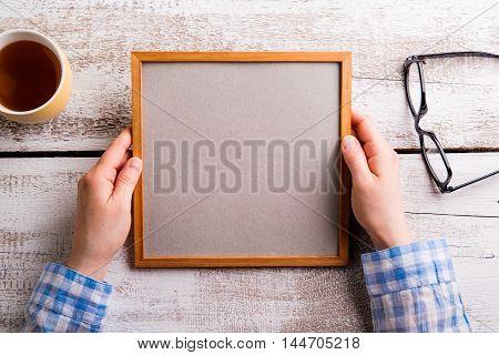 Unrecognizable Woman Holding Empty Picture Frame, Studio Shot.