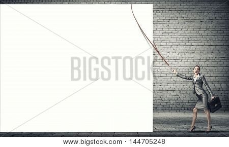 Young businesswoman pulling white banner with lead