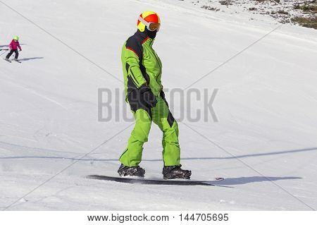 Man in a green overalls snowboarding on snow in the mountains on small child skiing in the background